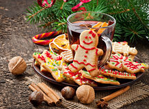 Warming mulled wine, spices and gingerbread cookie. On a wooden background in rustic style royalty free stock images