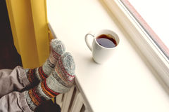 Warming by the radiator and drinking hot tea Stock Images