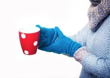 Warming red mug of tea. Girl holding a mug blue gloves Stock Photography