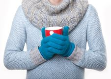 Warming red mug of tea. Girl warm gloved hands on a mug Royalty Free Stock Image