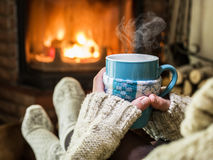 Warming and relaxing near fireplace. Royalty Free Stock Photography