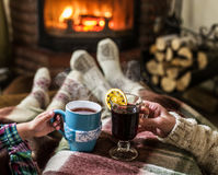 Warming and relaxing near fireplace with a cup of hot drink. Stock Image