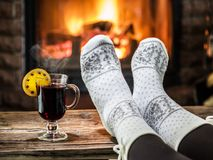 Warming and relaxing near fireplace with a cup of hot wine. Warming and relaxing near fireplace. Woman feet near the cup of hot wine in front of fire royalty free stock photos