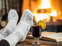 Warming and relaxing near fireplace with a cup of hot wine and a. Warming and relaxing near fireplace. Woman feet near the cup of hot wine and a book in front of stock photography