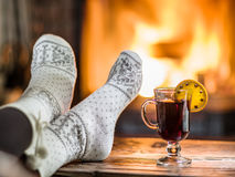 Warming and relaxing near fireplace with a cup of hot wine. Warming and relaxing near fireplace. Woman feet near the cup of hot wine in front of fire stock image