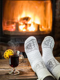 Warming and relaxing near fireplace with a cup of hot wine. Royalty Free Stock Photo
