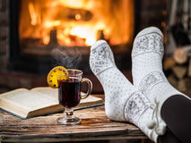 Warming and relaxing near fireplace with a cup of hot wine. Warming and relaxing near fireplace. Woman feet near the cup of hot wine in front of fire stock photography