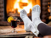 Warming and relaxing near fireplace with a cup of hot wine. Warming and relaxing near fireplace. Woman feet near the cup of hot wine in front of fire stock photos