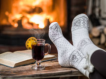 Warming and relaxing near fireplace with a cup of hot wine. Warming and relaxing near fireplace. Woman feet near the cup of hot wine in front of fire royalty free stock images