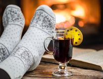 Warming and relaxing near fireplace with a cup of hot wine and a. Warming and relaxing near fireplace. Woman feet near the cup of hot wine in front of fire royalty free stock image