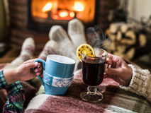 Warming and relaxing near fireplace with a cups of hot drink. Royalty Free Stock Images