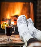 Warming and relaxing near fireplace with a cup of hot wine. Warming and relaxing near fireplace. Woman feet near the cup of hot wine in front of fire royalty free stock photography