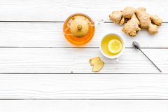 Warming tea with lemon and ginger. Cup, teapot, ginger root on white wooden background top view copy space Stock Photography