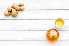 Warming tea with lemon and ginger. Cup, teapot, ginger root on white wooden background top view copy space Stock Image