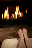Warming toes by the fire Stock Photos