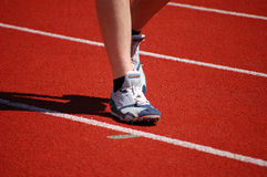 Warming Up. Athlete in running shoes walking on the running track Stock Photo