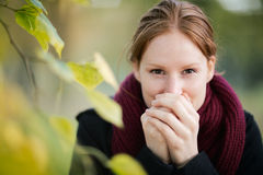 Warming Up Cold Hands in the Fall. A young woman warms up her hands with her own breath as she looks at the camera. Photographed in a park in the Autumn or Fall Royalty Free Stock Photos