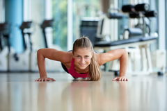 Warming up and doing some push ups a the gym. Gorgeous blonde woman warming up and doing some push ups a the gym stock photo
