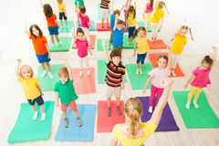 Warming-up during gymnastic lesson for kids in gym royalty free stock photos