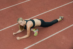 Warming up in the running lane. Attractive blond athlete stretching hip flexors on the track Stock Image