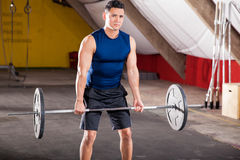 Warming up with some weights. Handsome Hispanic man lifting a barbell in a cross-training gym Stock Image