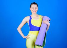 Warming up before training. Athlete yoga coach. Yoga class concept. Yoga hobby and sport. Practicing yoga every day. Girl slim fit athlete hold fitness mat stock image