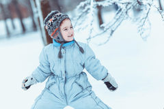 Warmly dressed boy playing in winter forest Stock Photo