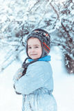 Warmly dressed boy playing in winter forest Stock Photos
