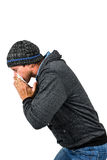 Warmly dressed man blowing his nose Stock Images