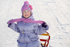 Warmly dressed smiling girl in pink scarf and hat looks up Royalty Free Stock Photo