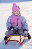 Warmly dressed smiling girl in pink scarf and hat sleds Stock Photo