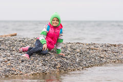 Warmly dressed smiling girl sitting on pebble near the sea and looking at the frame Royalty Free Stock Photo