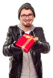 Warmly Dressed Young Man Handing Wrapped Gift Out Royalty Free Stock Images