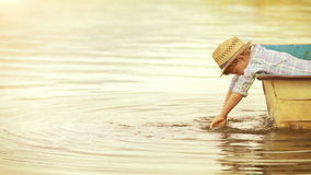 Warmly toned golden footage: wee boy in a trendy hat dangles his hands in the water being in the boat himself. stock video