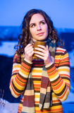Warmness for cold nights. Half length portrait of a fashionable brunette enjoying hot drink Stock Image