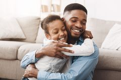 Warmth Hug. African Daughter Embracing Father With Love. And Tenderness stock image