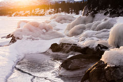 Warmth of orange sunlight on ice covered rocks Royalty Free Stock Photography