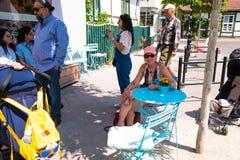 Warnemunde,戴着桃红色帽子的G妇女在蓝色圆桌上在一个街道咖啡馆在这个旅游镇坐这热的天在6月 免版税库存图片