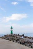 WARNEMUNDE, ALEMANIA - CIRCA 2016: Un faro del verde dirige las naves a esta ciudad alemana popular del puerto del día de fiesta  imagenes de archivo