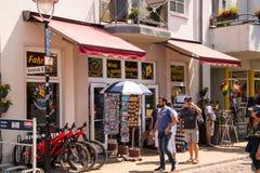Warnemunde, Allemagne - 8 juin 2018 : Une vue des touristes marchant après une boutique de souvenirs et une bicyclette de locatio images libres de droits