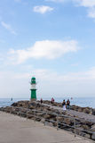 WARNEMUNDE, GERMANY - CIRCA 2016: A green lighthouse guides ships to this popular German holiday port town on the Baltic Sea. Near Rostock Stock Images