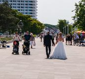 Bride and groom in wedding gown and tuxedo walk past a couple with two children in strollers on the sidewalk in this tourist town royalty free stock photos