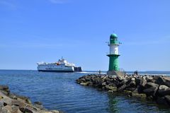 A large ferry is seen leaving the port of Warnemunde, Germany as it passes a small green lighthouse on this date royalty free stock images