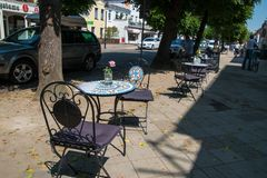 Round cafe tables on sidewalk in front of a restaurant stock image