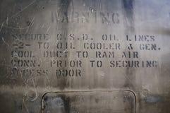 Warnen auf der Seite eines alten Flugzeuges Lizenzfreie Stockfotografie