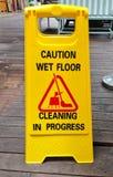 Warnen Sie das nasse Bodenzeichen, das laufendes Zeichen auf Holzfußboden säubert Stockbild
