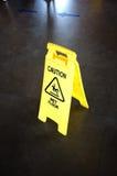 Warnen Sie gelbes Zeichen für nasse Bodenwarnung auf einem Boden Lizenzfreies Stockbild