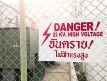 Warnende Gefahrenhochspannungszeichen und thailändische Sprache bedeuten Gefahr h Stockbilder