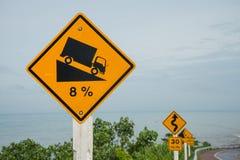 Warnende steile Verkehrsschildsteigung und -lKW auf Hügel Stockfotos