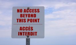 Warning. English-French bilingual sign, red on white against a cloudy sky: No access beyond this point-Acces interdit Royalty Free Stock Photo